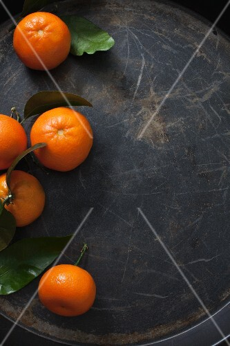 Five clementines with leaves