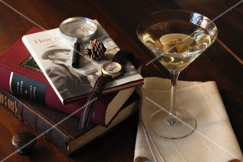 A dry martini with olives and classic books in a den