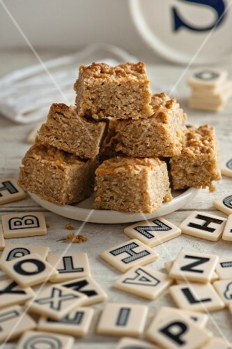 Flapjacks on a plate surrounded by letter tiles