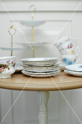 Vintage crockery (plates, cups and a cake stand) on a table