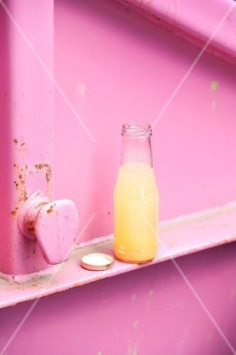 A bottle of homemade peach lemonade with basil