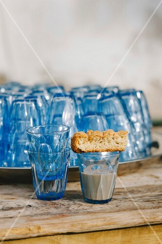 A buttermilk rusk on a glass with blue glasses in the background