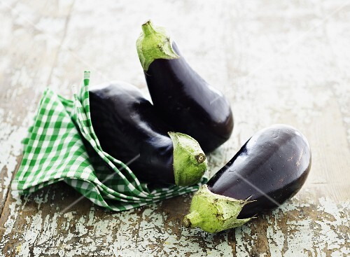 Three aubergines with a checked towel