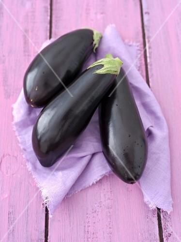 Three aubergines on a purple cloth