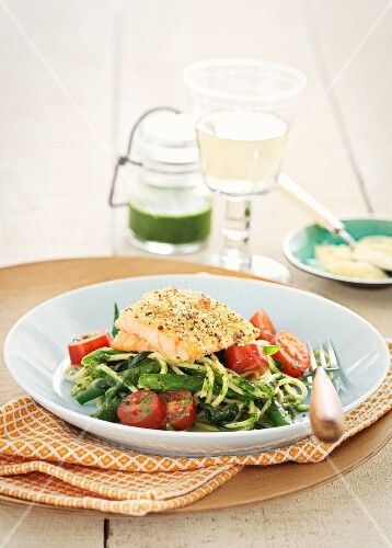Steamed salmon fillet on spaghetti with green asparagus and tomatoes