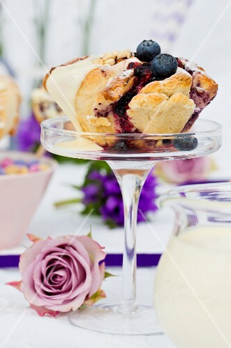 A spiral cake with blueberries and vanilla sauce on a glass stand