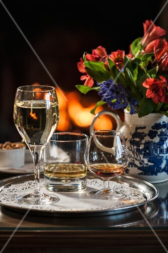 A glass of white wine, a whiskey and cognac on a tray