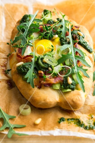 A ham and bacon pizza with egg, herbs, rockets, pine nuts, pesto and onions