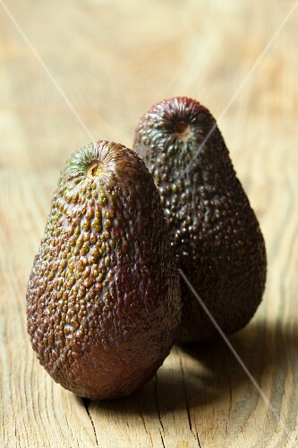 Two avocados on wooden background