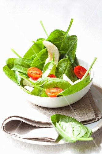Spinach salad with goat's cheese, pears, cherry tomatoes and balsamic vinegar