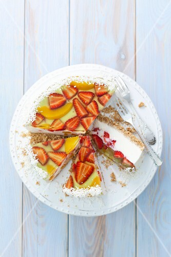 Vanilla yoghurt cheesecake with fruit jelly, strawberries, peaches and coconut