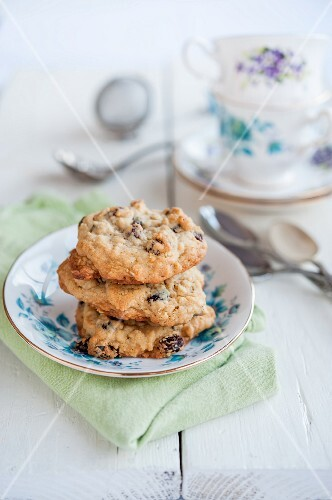 A stack of chocolate chip cookies with tea cups in the background