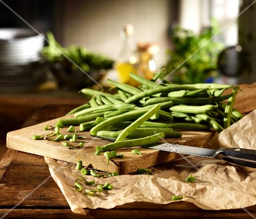 Green beans being chopped on a wooden board in a kitchen