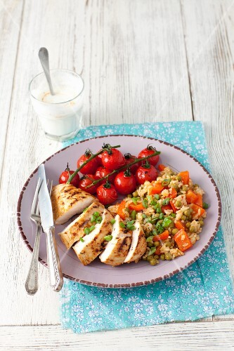 Grilled chicken breast with a rice, peppers and pea salad