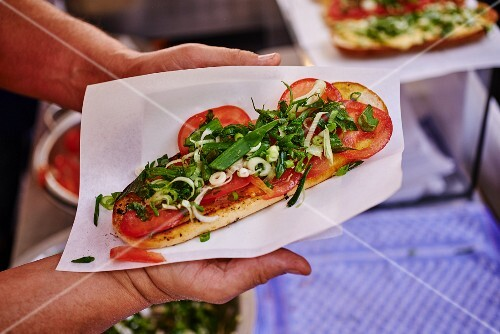 Hands holding a tomato and garlic baguette