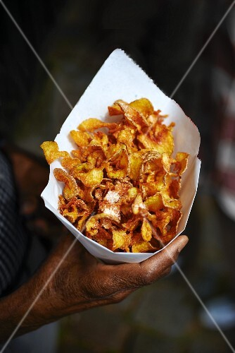 Hands holding a cone of crisps