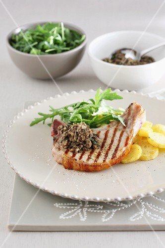 A grilled chop with potato and rocket salad