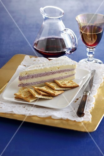 Brie with a cranberry cream filling served with crackers and red wine