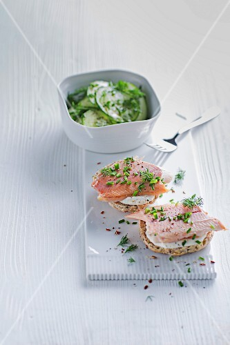 A herb bread roll topped with smoked trout served with a cucumber salad