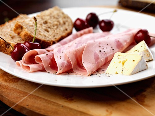 Slices of beer ham, soft cheese, cherries and bread
