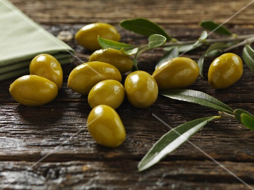 Green olives with leaves on a wooden surface