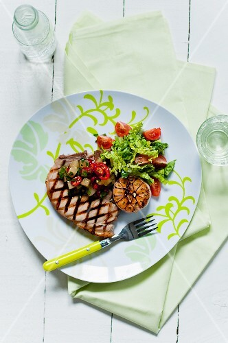A grilled pork chop with salad, garlic and pineapple salsa