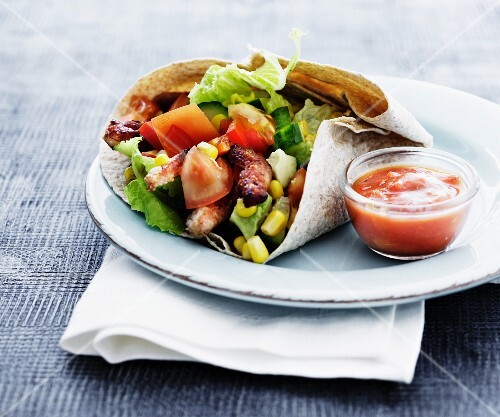 A wrap with vegetables and grilled meat