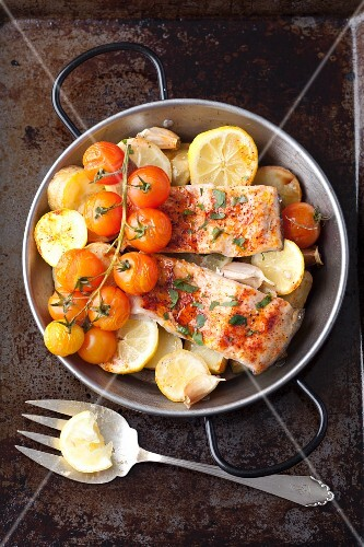Oven-baked salmon trout with potatoes, lemons and cherry tomatoes
