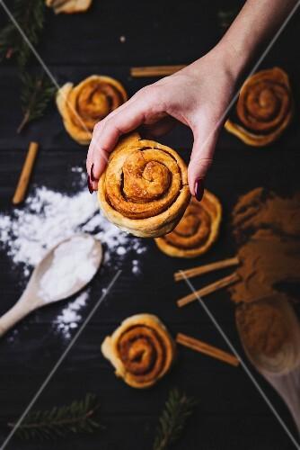 A hand holding a cinnamon bun (Christmas)