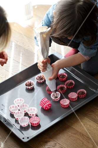 A child piping chocolate muffin mixture into mini paper cases