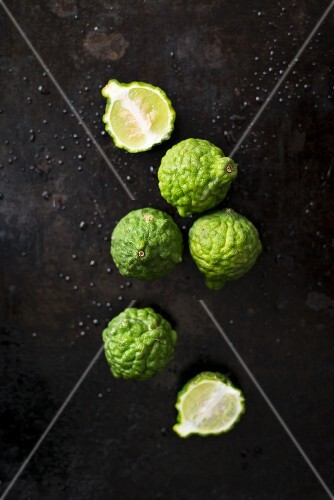 Kaffir limes, whole and halved on a black background (seen from above)