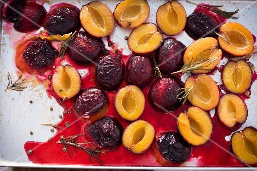 Oven roasted damsons with rosemary on a baking tray (seen from above)