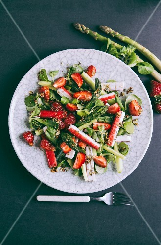 Spring salad with strawberries, surimi, green asparagus and cucumber
