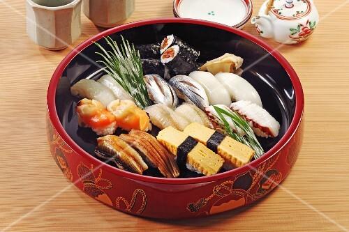 Various nigiri and maki in a ceramic bowl (Japan)