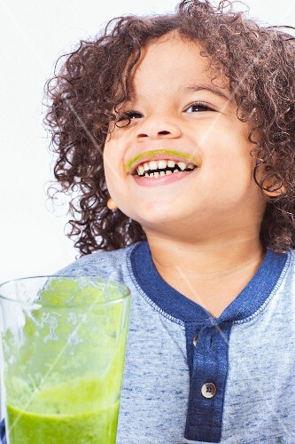 A boy drinking a green smoothie with smeared lips