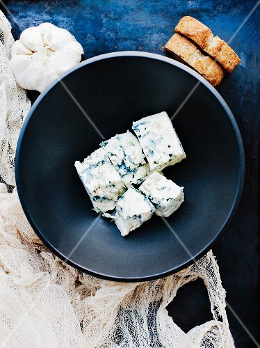 Diced blue cheese in a bowl with a garlic bulb and slices of bread next to it