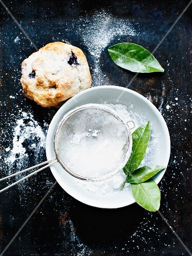 A blueberry scone and icing sugar