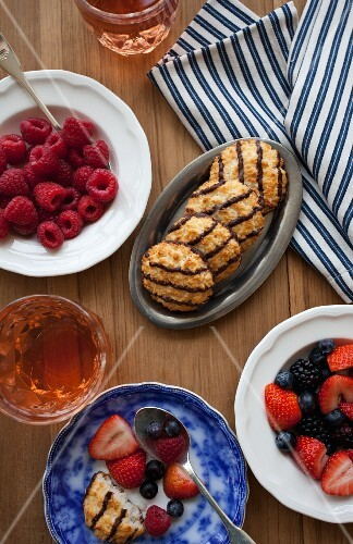 Fresh berries, coconut and chocolate macaroons, mango iced tea and a striped tea towel