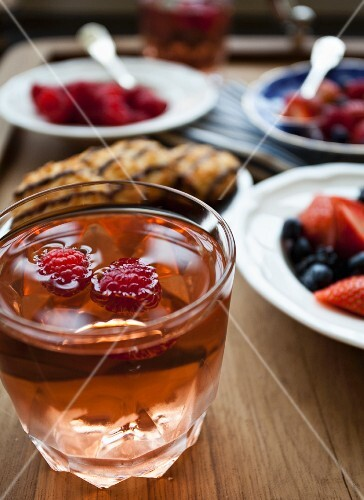 A glass of cold mango lemonade with raspberries