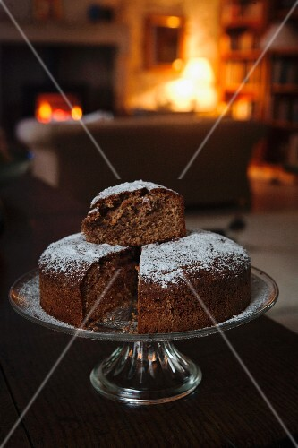 Hazelnut chocolate cake on a cake stand in a room with a fireplace