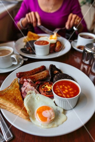 An English breakfast with egg, sausage, beans, vegetables and toast (England)