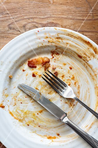An empty plate with dirty cutlery
