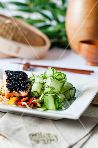 Steamed salmon with a black sesame crust on noodles, with stir-fried vegetables and fresh cucumber salad