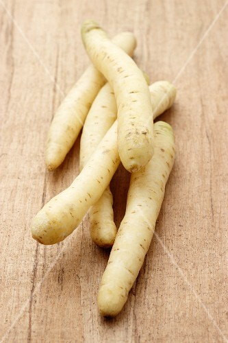 White carrots on a wooden surface