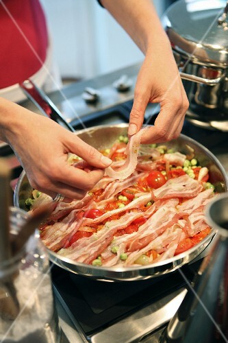 Bacon being added to a pan of fried vegetables