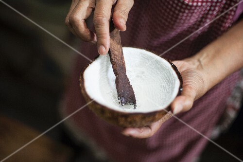 Coconut marrow being scratched out of a coconut shell with a wooden stick