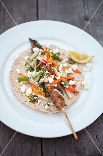 A minced turkey skewer, pickled vegetables and feta cheese on unleavened bread