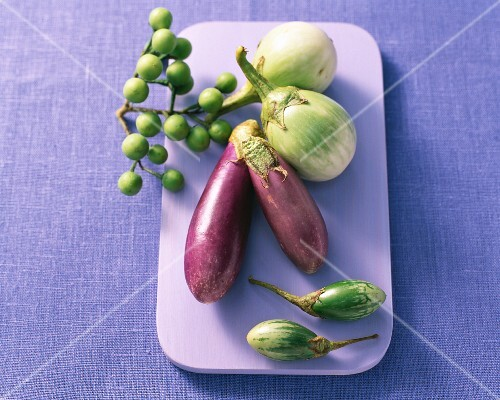 Various types of aubergines on a purple chopping board