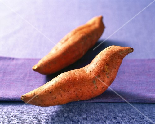 Two sweet potatoes on a purple surface