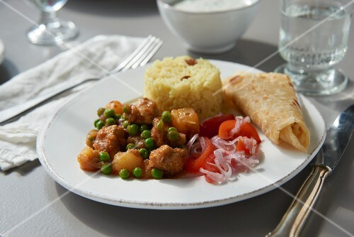 Chicken curry with peas, tomato salad and rice (South Africa)